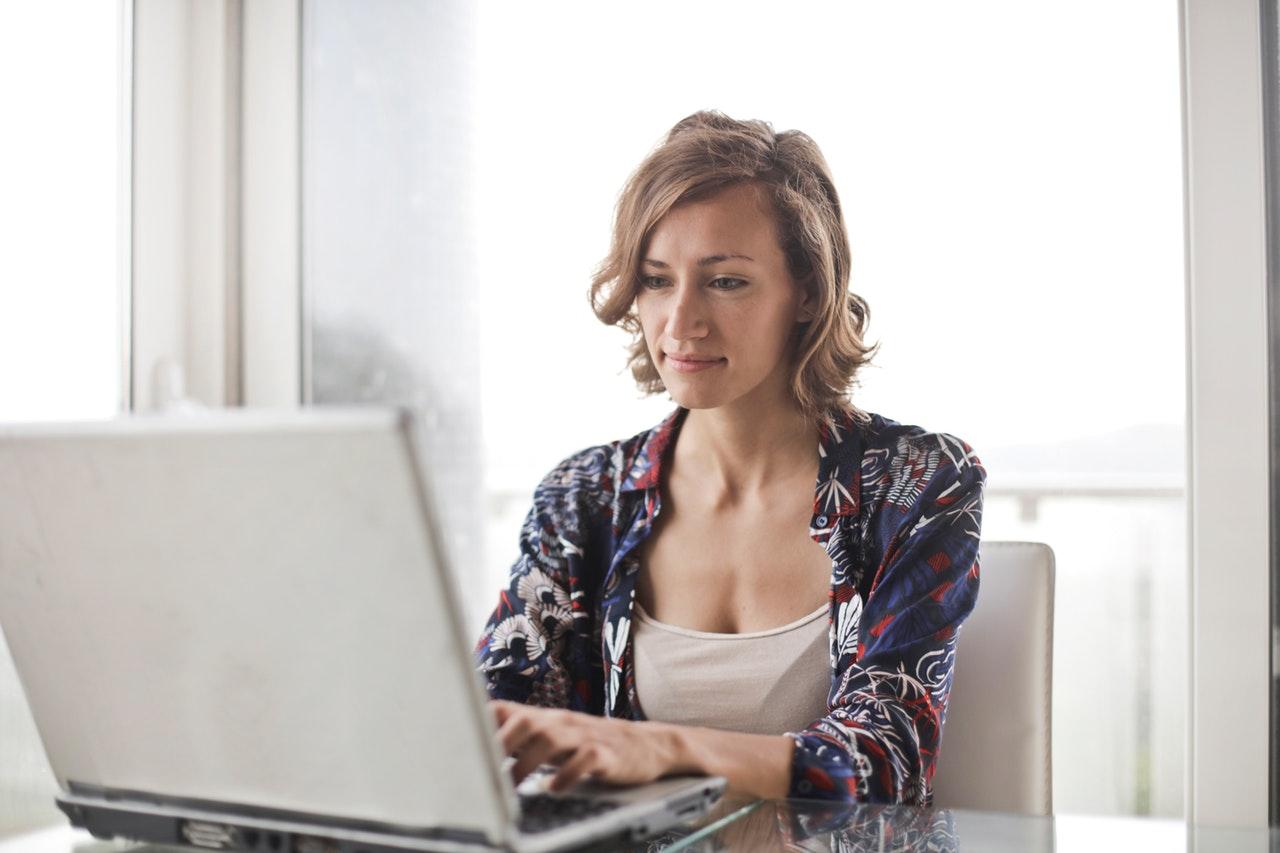 Dame i blå bruger computer