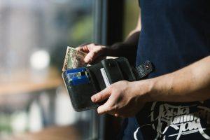 Sort læder pung holdt af tyv der stjæler